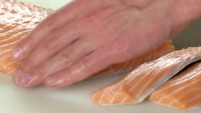 Hands cutting fish close up. Sliced fresh salmon stock footage