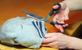 Hands cutting material with shears or scissors. Royalty Free Stock Photos