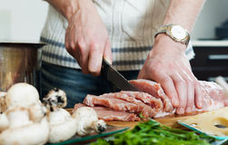 Hands cutting meat Royalty Free Stock Photo