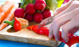Hands cutting pepper on a cutting board Stock Photos