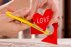 Hands cutting a red paper heart, closeup Royalty Free Stock Photography