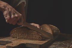 Hands cutting rye bread Stock Photos