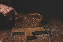 Hands cutting rye bread Stock Image