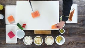 Hands cutting salmon top view. Kitchen table, sushi preparation stock footage