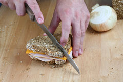 Hands cutting sandwich. Hands cutting turkey sandwich on countertop Royalty Free Stock Images