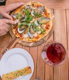 Hands cutting a seafood pizza with New Zealand NZ green lipped m Stock Photos