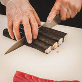 Hands cutting sushi rolls with knife Stock Image
