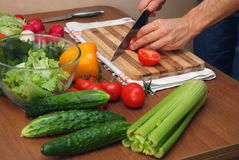 Hands cutting vegetables on kitchen table Royalty Free Stock Photos