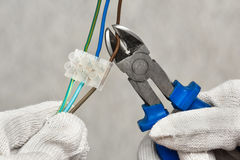 Hands cutting wires with clippers Royalty Free Stock Photo