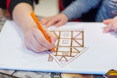 Hands of dad and little child drawing  picture of house. Hands of dad and little child drawing together picture of house. Family home concept Royalty Free Stock Images