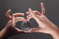 Hands with dark background. Hands holding glass globe with a shape of heart fingers joint together Royalty Free Stock Photo