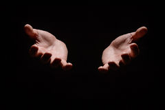 Hands from the dark. Close-up of human hands stretching out from Royalty Free Stock Image