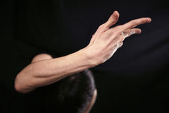 Hands in the dark. Empty man pointing finger on black dark background Royalty Free Stock Images