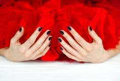 Hands with dark manicure and red veiling Stock Image
