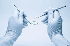 Hands of dentist holding his tools Stock Photo