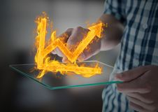 Hands with device with graph fire icon over. Blurred office background Stock Photo