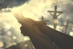 Hands of a devout person holding God`s hand. S in the sky with three crucifixes in the background stock photo