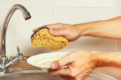 Hands with dirty dishes over the sink in kitchen Stock Photography
