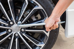 Hands disassembling a modern car wheel (steel rim) with a lug wrench Stock Images