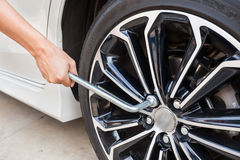 Hands disassembling a modern car wheel (steel rim) with a lug wrench Royalty Free Stock Image