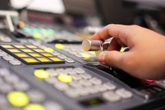 Hands on  dissolve of Switcher buttons in studio TV station, Aud. Io and Video Production Switcher of Television Broadcast Royalty Free Stock Photo