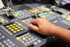Hands on dissolve of Switcher buttons in studio TV station, Audi. O and Video Production Switcher of Television Broadcast Royalty Free Stock Photo