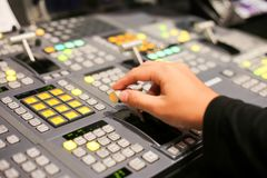 Hands on dissolve of Switcher buttons in studio TV station, Audi. O and Video Production Switcher of Television Broadcast Stock Photography