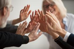 Hands of diverse business people giving high five, close up. Hands of diverse business people giving high five, smiling team members, teachers and students royalty free stock image