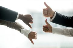 Hands of diverse business people showing thumbs up and down royalty free stock images