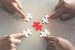 Hands of diverse people assembling jigsaw puzzle, help support stock photography