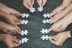 Hands of diverse people assembling jigsaw puzzle, team put pieces together searching for right match, help support in teamwork to stock images