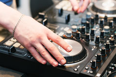 Hands on the DJ decks. Man makes music for dancing in the club. Mixer with vinyl record at party royalty free stock photo