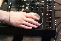 Hands on the DJ decks. Man makes music for dancing in the club. Mixer with vinyl record at party stock image