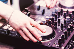Hands on the DJ decks. Man makes music for dancing in the club. Mixer with vinyl record at party royalty free stock image
