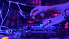 The hands of a DJ performing in a nightclub at a party. disco lights stock footage