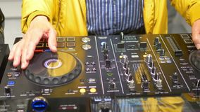 Hands of DJ on sound console