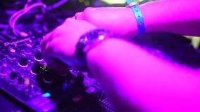 Hands of DJ tweak various track controls on dj`s deck stock video footage