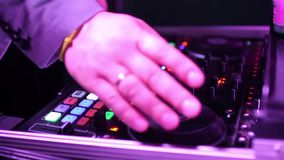 Hands of DJ tweak various track controls on dj`s deck. Hands of DJ which mixes music tracks with CD-players and mixer in nightclub stock video