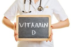 Hands of a doctor holding a blackboard with the workds Vitamin D stock images
