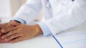 Hands of doctor supporting senior woman at clinic stock footage