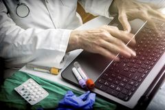 Hands of doctor writing fast on laptop stock photography