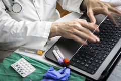 Hands of doctor writing fast on laptop stock images
