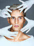 Hands of doctors in medical gloves touching face of beautiful young man stock image