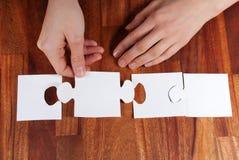 Hands doing a puzzle. Two hands doing a puzzle with copyspace on it Stock Photo