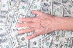 Hands on dollar bills. Old hands on dollar bills Stock Photos