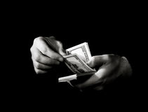 Hands with dollars over black Royalty Free Stock Photos