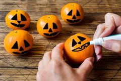 Hands draw a face on a tangerine on Halloween stock photography