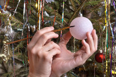 Hands drawing on Christmas ball on Christmas tree background Royalty Free Stock Photography