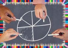 Hands drawing pie chart on blackboard with coloring pencils. Digital composite of Hands drawing pie chart on blackboard with coloring pencils Stock Images