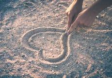 Hands draws heart. Instagram stylisation. Woman`s hands draws heart on the sand. Instagram stylisation Stock Photo